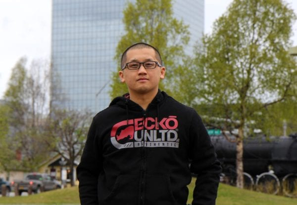 A man in a hoody andd a glasses and short hair stands looking at the camera
