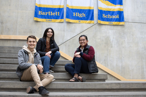 three high school students sit on steps and smile at the camera