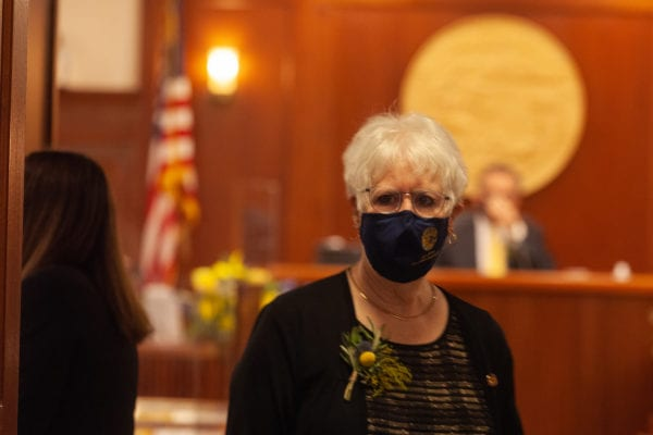A white woman with white hair wearing a mask walks in a ood panelled room