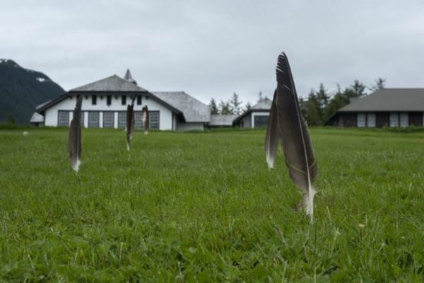 Eagle feathers stuck in a law in front of a white building