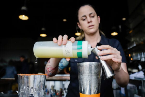 a person prepares a mixed drink at a restaurant bar