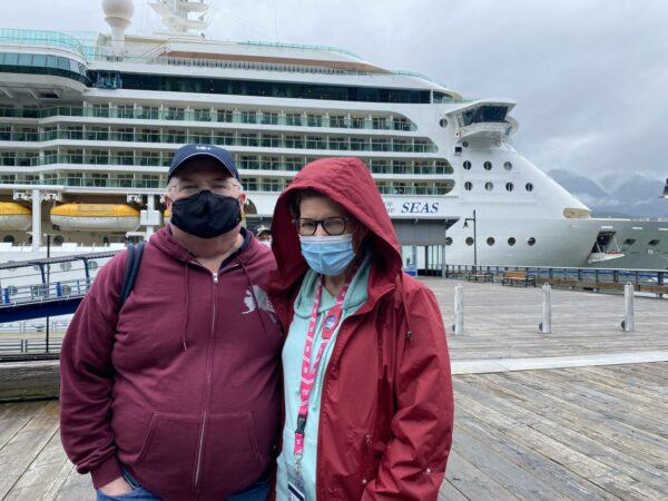 Two people stand in zipper-up jackets and sweatshirts in front of a cruise ship.