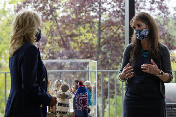 Two women wearing face masks talk inside, near big windows.