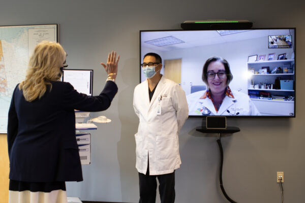 A woman waves at another woman who appears on a screen.