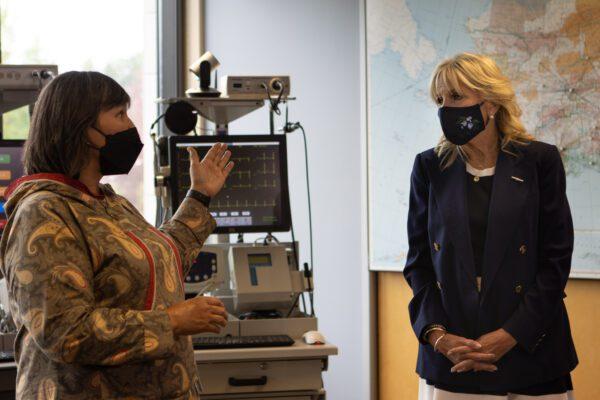 Two women talk, both wearing face masks, near medical equipment.