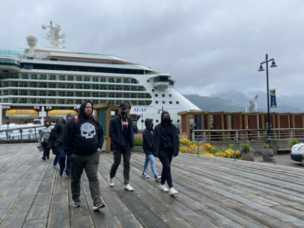 People walk on a dock, with a cruise ship in the background.
