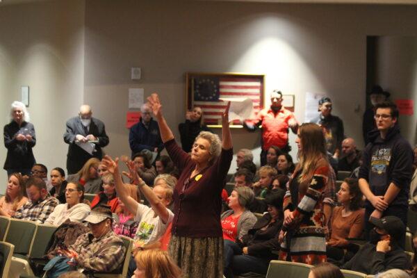 crowd raises hands