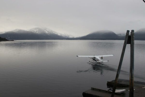 A float plane sits on the water in an overcast day.